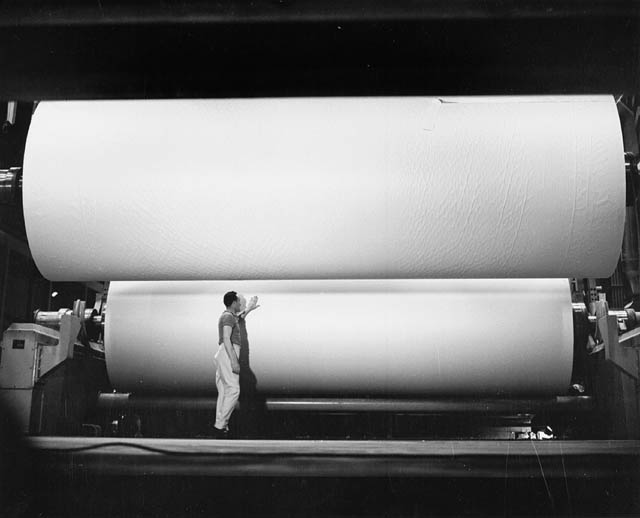 Man beside giant roll of paper