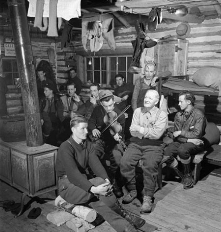 Lumbermen sitting around and enjoying violin music played by lumberman Romeo Clement of Farley Quebec in their bunk house